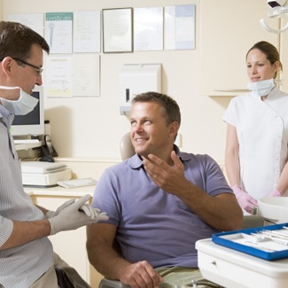 Man talking to dentist in exam room