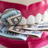 A mold of a mouth biting down on money and a dental mirror