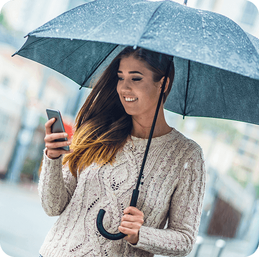 Smiling Woman holding umbrella & using phone