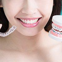 woman holding invisalign and traditions braces