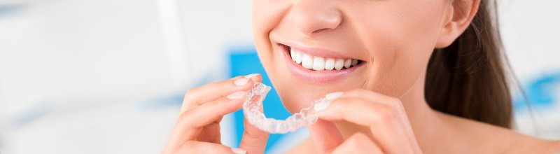 young woman smiling inserting Invisalign aligner