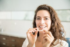 Woman holding Invisalign clear aligner.