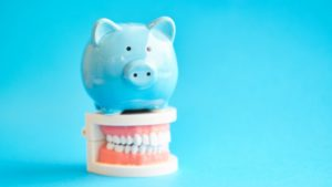 Blue piggy bank of dental insurance sitting on model teeth