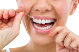 woman smiling using dental floss
